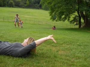 Rosie and families rolling down a hill at Kenwood